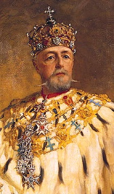 An elderly, bearded man in ornate robes, wearing a jewelled crown surmounted by a cross, looks straight out of the picture.