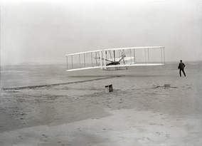 First flight of the Wright Flyer, December 17, 1903, Orville piloting, Wilbur running at wingtip.