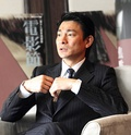A serious-looking Andy Lau, seated and wearing a suit