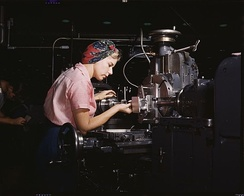 Machine tool operator at the Douglas Aircraft plant, Long Beach, California in World War II. After losing thousands of workers to military service, American manufacturers hired women for production positions, to the point where the typical aircraft plant's workforce was 40% female.[14]
