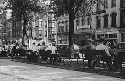 A dozen men in hats sitting on public benches facing an avenue of older stone buildings