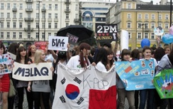 K-pop fans in Warsaw holding a South Korean-Polish flag as well as banners of various boy bands