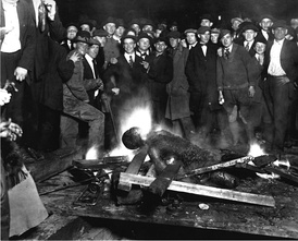 A group of white men pose for a 1919 photograph as they stand over the black victim Will Brown who had been lynched and had his body mutilated and burned during the Omaha race riot of 1919 in Omaha, Nebraska