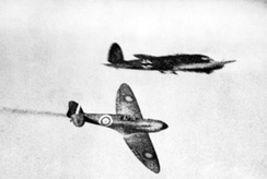 British Supermarine Spitfire fighter aircraft (bottom) flying past a German Heinkel He 111 bomber aircraft (top) during the Battle of Britain in 1940
