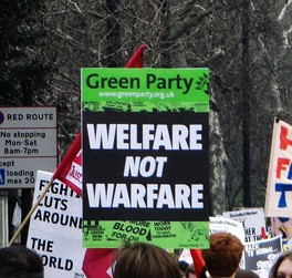 """Welfare not Warfare"" sign, indicating the Green Party's policy towards social justice and non-violence"