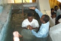 An Adventist pastor baptizes a young man in Mozambique.