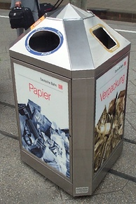 A three-sided bin at a railway station in Germany, intended to separate paper (left) and plastic wrappings (right) from other waste (back)