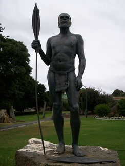 Mokare with spear and woomera, another woomera lies at his feet.