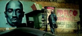 As Jay-Z and Beyoncé share an intimate moment in a phone-booth, a spray-painted mural is displayed, tributing Tupac Shakur.