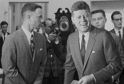 Black-and-white film screenshot showing the main character on the left looking towards another man, President Kennedy, (voiced by actor Jed Gillin), on the right. Kennedy is smiling and looking to his left. In the background, several men are looking in different directions and one is aiming a camera.