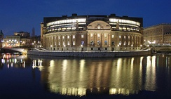 The Riksdag building exterior, from the west, at night.