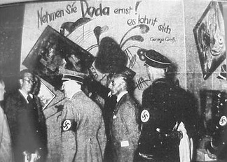 Adolf Hitler and Adolf Ziegler visit the Degenerate Art Exhibition, 1937. The wall behind them calls attention to the works of the Dada artists with depreciatory comments.