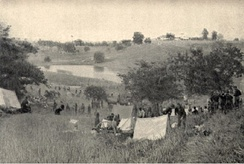 US Army encampment, 1st Volunteer Cavalry, Rough Riders, at the base of Kettle Hill about July 5, 1898. San Juan Hill and block houses are in background.