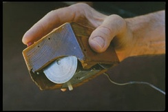 Inventor Douglas Engelbart holding the first computer mouse,[7] showing the wheels that make contact with the working surface