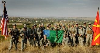 Vermont National Guard members supporting Operation Rising Phalanx stand with U.S. and Macedonian troops holding the Green Mountain Boys battle flag in the Republic of Macedonia.