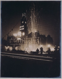 The Sydney Town Hall illuminated in celebratory lights and fireworks marking the Inauguration of the Commonwealth of Australia, 1901. The sign reads One people, one destiny.