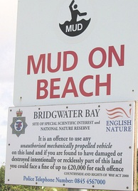 Mud danger signs on Bridgwater Bay near the mouth of the River Parrett are necessary because fast, high-amplitude tides here have led to drownings on the extensive mud flats.