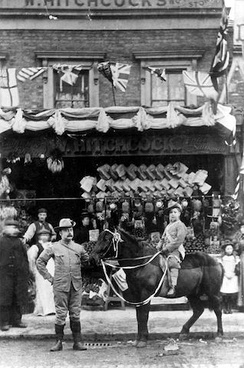 "William Hitchcock, probably with his first son, William, outside the family shop in London, c. 1900; the sign above the store says ""W. Hitchcock"". The Hitchcocks used the pony to deliver groceries."