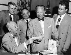 "Dave Jones hands a check for $250,000 to Arthur B. ""Mickey"" McBride as a down payment on the purchase of the Browns for $600,000.[55]"