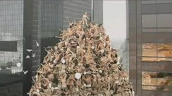 Still from the music video showing Minogue standing atop a pyramid of underwear-clad couples, which was inspired by the installations of American photographer Spencer Tunick.[69]