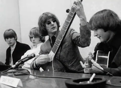 "The Byrds at the ""Eight Miles High"" press conference in March 1966, posing with a sitar in order to illustrate the Indian influences present in the song."