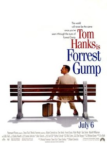 Film poster with a white background and a park bench (facing away from the viewer) near the bottom. A man wearing a white suit is sitting on the right side of the bench and is looking to his left while resting his hands on both sides of him on the bench. A suitcase is sitting on the ground, and the man is wearing tennis shoes. At the top left of the image is the film's tagline and title and at the bottom is the release date and production credits.