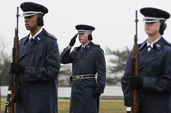 A USAF HG firing party renders honors during a funeral at Arlington National Cemetery.