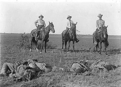 Capt. Monroe Fox and two other Rangers on horseback with their lariats around the bodies of dead Mexican bandits, after the Norias Ranch Raid August 8, 1915