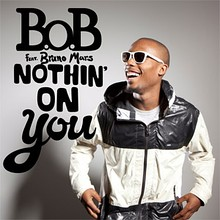 "A picture of B.o.B standing up on the left of the image while laughting, with the words ""B.o.B feat. Bruno Mars Nothin' on You"" with capital font on the right of B.o.B"