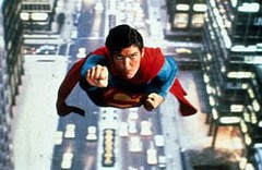 Publicity still emulating screen shot in which Superman (Christopher Reeve), with his traditional suit, flies toward the sky, with Metropolis underneath him.