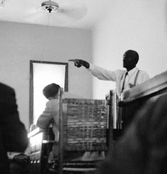 "Till's uncle, Mose Wright, identifying J. W. Milam during Milam's trial, an act which ""signified intimidation of Delta blacks was no longer as effective as the past"".[85] Wright had ""crossed a line that no one could remember a black man ever crossing in Mississippi.""[86]  Photojournalist Ernest Withers defied the judge's orders banning photography during the trial to capture this shot."
