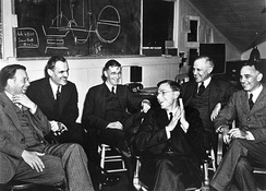 Six men in suits sitting on chairs, smiling and laughing