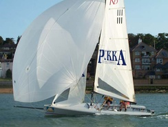 RS K6 keelboat with an asymmetric spinnaker on a retracting bowsprit.