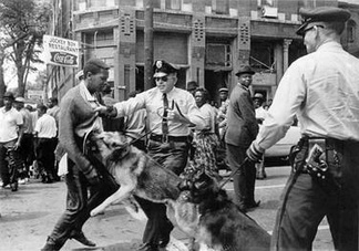 A black-and-white photograph of a black male teenager being held by his sweater by a Birmingham policeman and being charged by the officer's leashed German Shepherd while another police officer with a dog and a crowd of black bystanders in the background look on
