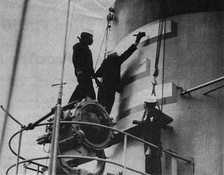 "Crewmembers paint a gold ""E"" on the stack of the USS Rankin"