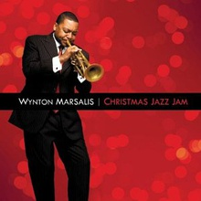 "Before a red background, a man in a suit is playing a trumpet with his eyes closed; the text ""Wynton Marsalis Christmas Jazz Jam"" appears in a black bar across the center"