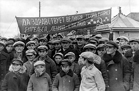 "Residents of a town in Eastern Poland (now West Belarus) assembled to greet the arrival of the Red Army during the Soviet invasion of Poland in 1939. The Russian text reads ""Long Live the great theory of Marx, Engels, Lenin-Stalin"" and contains a spelling error. Such welcomings were organized by the activists of the Communist Party of West Belarus affiliated with the Communist Party of Poland, delegalized in both countries by 1938.[127]"
