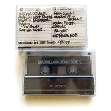 Photo of the front and back sides of two of the demo tape's cassettes against a white background.