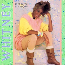 "A woman is sitting, with a smile on her face. She is looking forward and her head is resting on her left arm. She is wearing bangles on her right wrist. Next to her the word ""Whitney"" is written in medium purple capital letters. The words ""How Will I Know"" are written near her head."