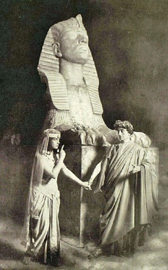 Stage photograph showing actor as Julius Caesar and actress as Cleopatra in Egyptian setting