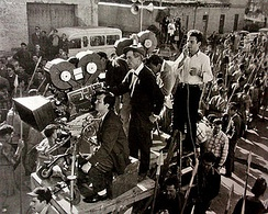 Director Stanley Kubrick looking through camera with cinematographer Russell Metty (in hat) standing behind, on set for Spartacus (1960).