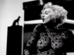 "Madonna wearing the controversial sheer lace blouse in the black and white ""Vogue"" music video."