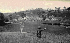 US Army photo taken near the base of Kettle Hill about July 4, 1898. The soldier is pointing up to the top of Kettle Hill. In the background are the block houses on San Juan Hill and the American encampment.