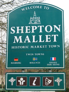 Green signs with white writing and symbols saying Welcome to Shepton Mallet, Historic Market Town, Twin Towns Misburg, Bollnas, Oissel sur Seine