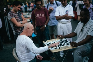 Spectators watch as a street chess player plays bullet chess with a customer in Union Square.