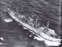 "Aerial photograph of the Liberty ship SS John W. Brown outbound from the United States carrying a large deck cargo after her conversion to a ""Limited Capacity Troopship."" It probably was taken in the summer of 1943 during her second voyage."