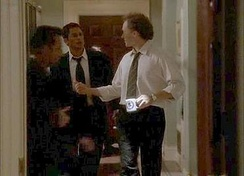 Sam Seaborn and Josh Lyman converse in the hallway in one of The West Wing's noted tracking shots.