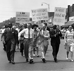 "A group of four middle-aged men in suits and one woman in a dress walk in the first rank of a procession of individuals down the middle of a street. Brick upper-stories of storefronts appear in the background, from middle to the right; tops of trees appear in the distance, far left. Three placards tacked onto pickets and held by two men in the second rank and one in the first rank read as follows. ""I Am John A. Maxwell I Was Discriminated Against In The Pointes."" ""The Freedoms We Lose May Be Your Own."" ""A House Holds No Prejudice."""
