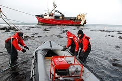 Coast Guardmen preparing to transport a portable pump to the 112-foot grounded fishing vessel Mar-Gun, March 7, 2009