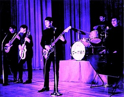 A tinted photograph of five members of the D-Men performing with guitars, drums and keyboards
